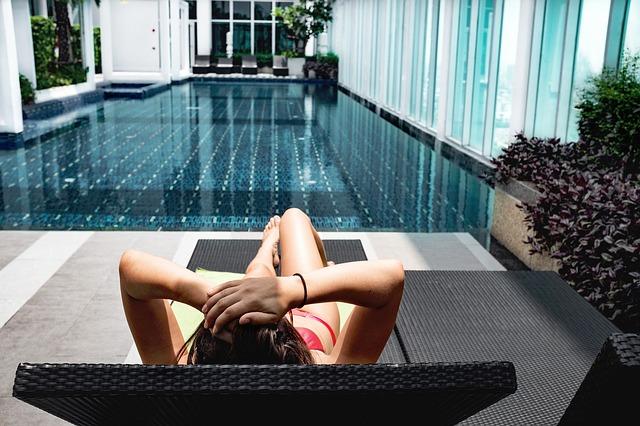 žena na lehátku u bazénu